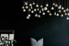 23 a branch with hanging down Christmas ornaments is a cool idea to decorate any space with modern vibes