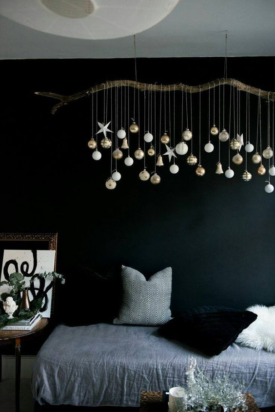 a branch with hanging down Christmas ornaments is a cool idea to decorate any space with modern vibes