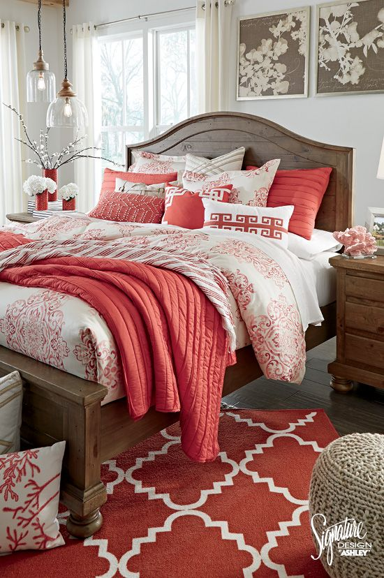 a bright bedding set with coral and white and lots of different prints and matching pillows and a rug cheer up a neutral space