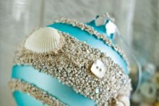 23 a turquoise Christmas ornament with beach sand, buttons and seashells can be DIYed