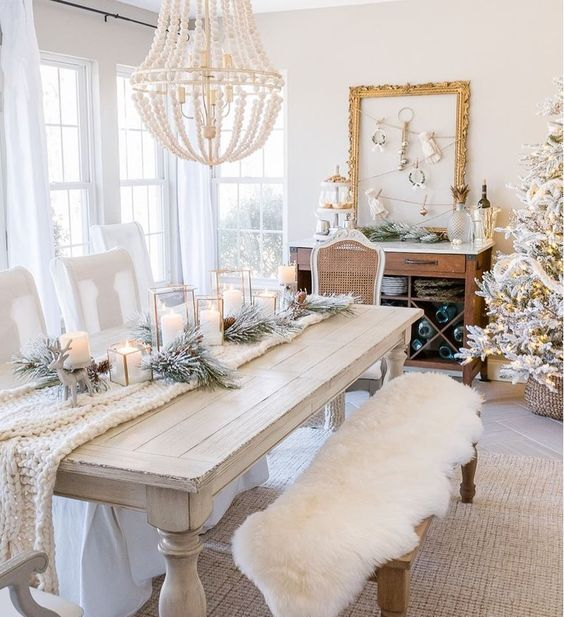 a white table setting with a knit throw, a faux fur throw on the bench and snowy evergreens