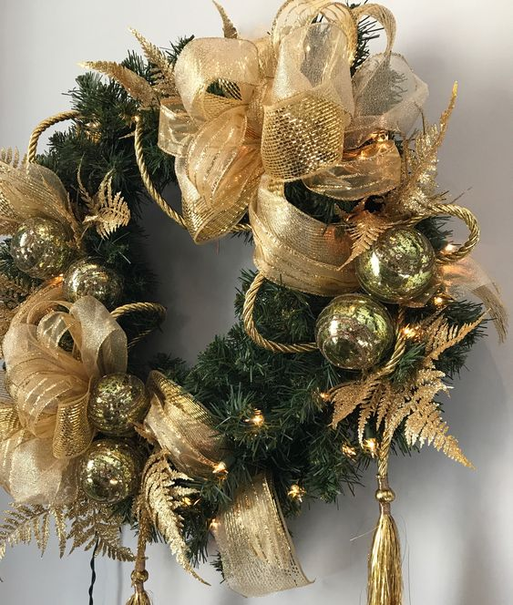 a lush and holiday Christmas wreath decorated with gold bows, tassels and ornaments