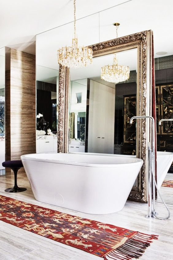 a mirror wall and an oversized refined vintage mirror over it to create a sophisticated space