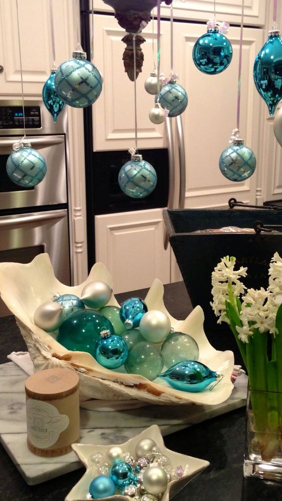 blue and turquoise Christmas ornaments hanging on a chandelier and in an oversized shell as a coastal display