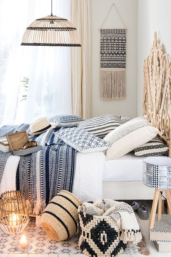 lots of printed textiles, wicker baskets, lamps, a headboard and a hanging make the bedroom Mediterranean at once