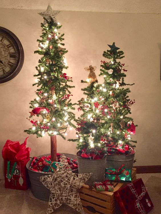 a trio of Christmas trees in galvanized buckets, with lights, red decor, stars and gifts all around