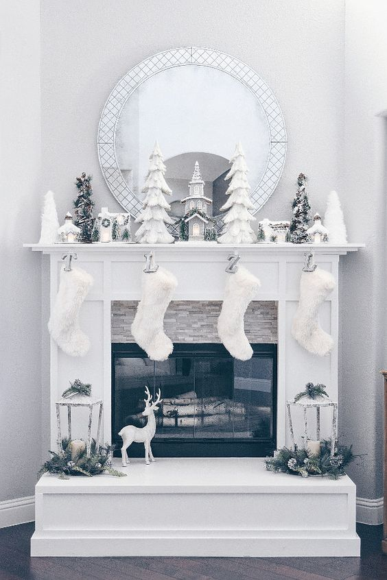 an all-white Christmas fireplace with stockings, lanterns, trees and snowy ornaments looks dreamy