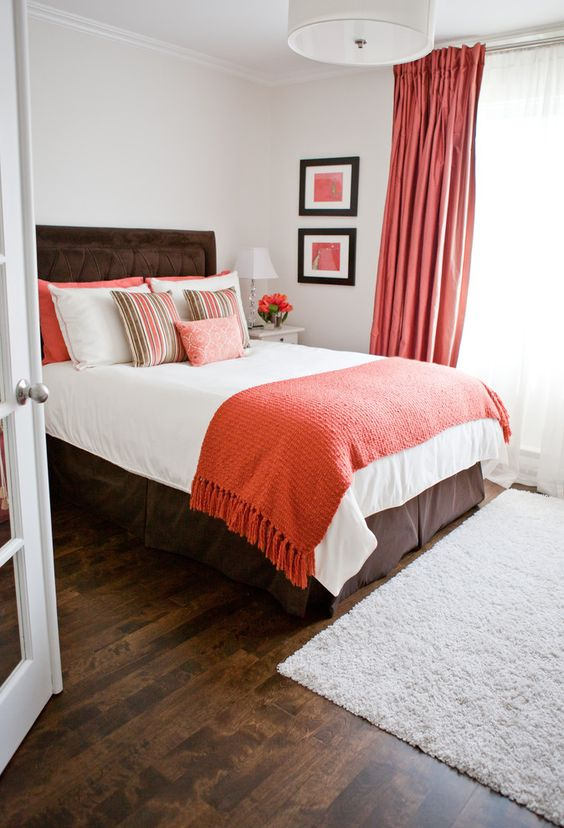 coral curtains, a coral throw and pillows add a trendy colorful touch to the bedroom and make it cheerful