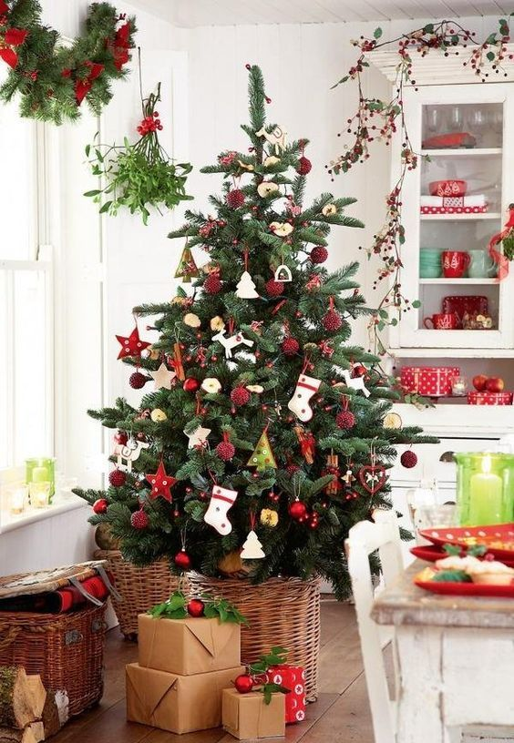 a cute Scandi-inspired Christmas tree in a basket with red ornaments and stockings plus gifts for coziness