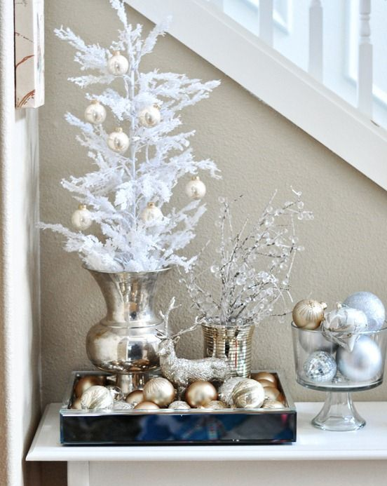 gold and silver ornaments can be displayed on white trees and branches, in bowls and jars for a frozen look