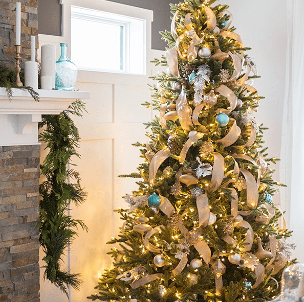 a Christmas tree done with metlalic and blue ornaments and burlap ribbons that give a rustic feel