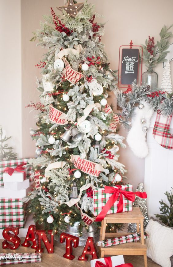 a classic Christmas tree with white ornaments, red berries, fabric blooms, bells and Merry Christmas ribbons all over