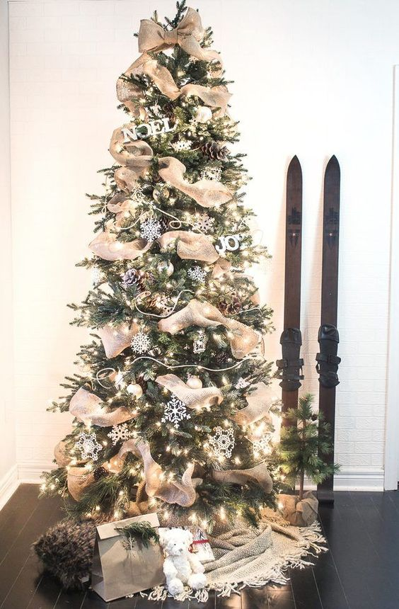 a cozy rustic Christmas tree decorated with snowflakes, pinecones, lights and burlap ribbons for a rustic feel