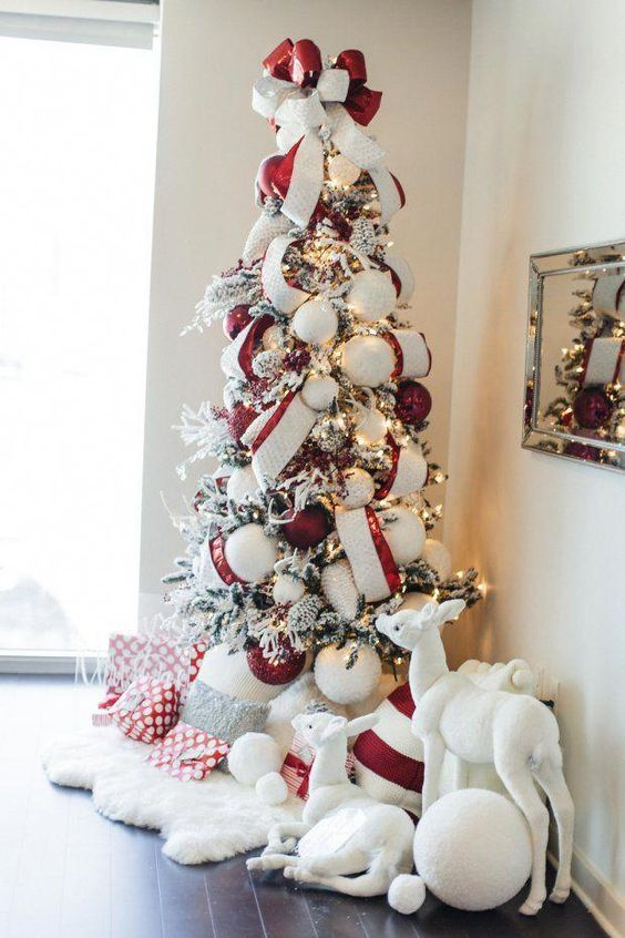 a cute and cozy flocked Christmas tree decorated with oversized white and red ornaments plus red and white ribbons