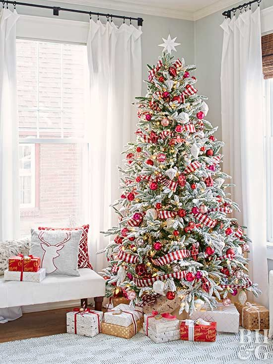a flocked Christmas tree with lights, red and metallic ornaments and red and white striped ribbons plus a star