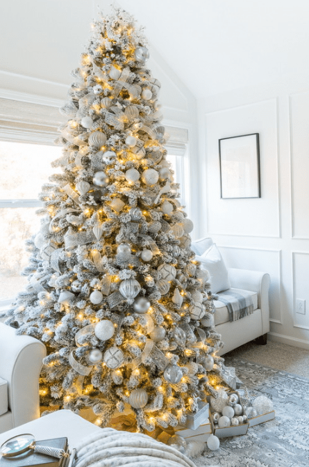 a flocked Christmas tree with metallic and white ornaments, lights and white and silver ribbons is a luxurious piece