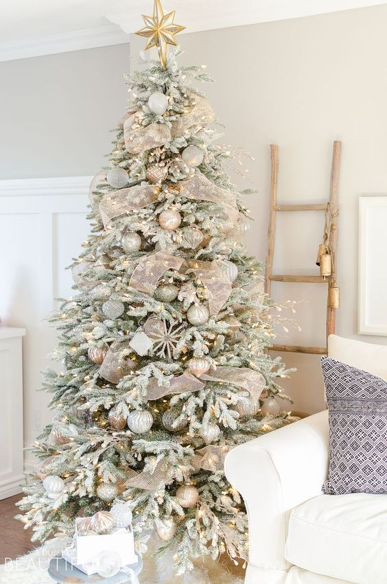 a snowy Christmas tree with lights, metallic ornaments and sheer gold ribbon plus a star on top
