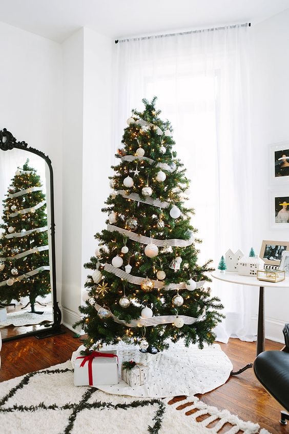 an elegant Christmas tree decorated with metallic ornaments, lights and black and white striped ribbons