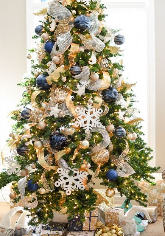 bold Christmas decor with oversized navy and gold ornaments, lights, snowflakes and gold and white ribbons for decor