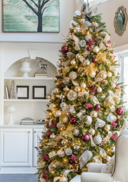 lush Christmas tree decor with lots of lights, metallic ornaments, white and burgundy ribbons and pinecones