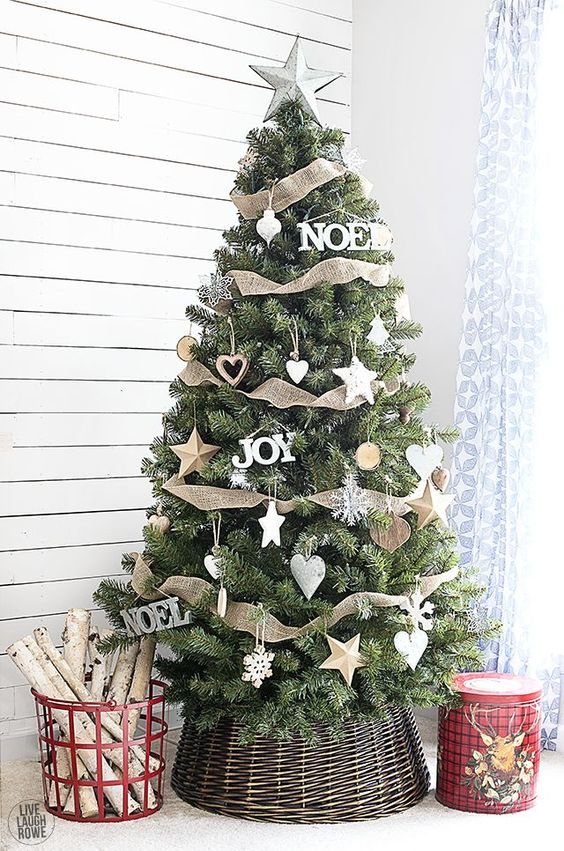rustic chic Christmas tree decor with wooden and white ornaments and burlap ribbons going horizontally with a star on top