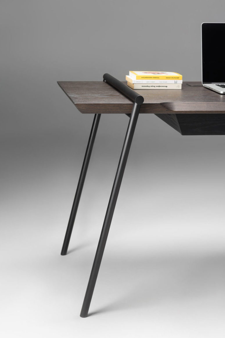 The desk is made of dark and stylish veneer, and there are matte black legs placed in a catchy way