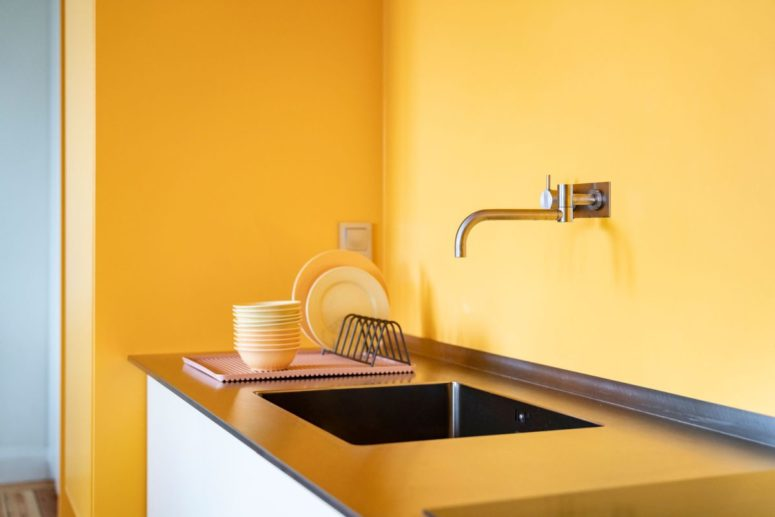 The warm yellow tone of the walls is reflected into the kitchen counter, adding a comfortable vibe to the decor