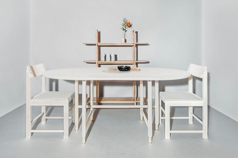 This is a dining table, chairs and an open shelving unit that all feature similar legs and curved angles that are characteristic features of the collection