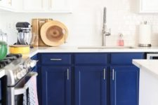 02 a chic and bold kitchen with navy cabinets and white countertops and mosaic navy and white tiles on the floor