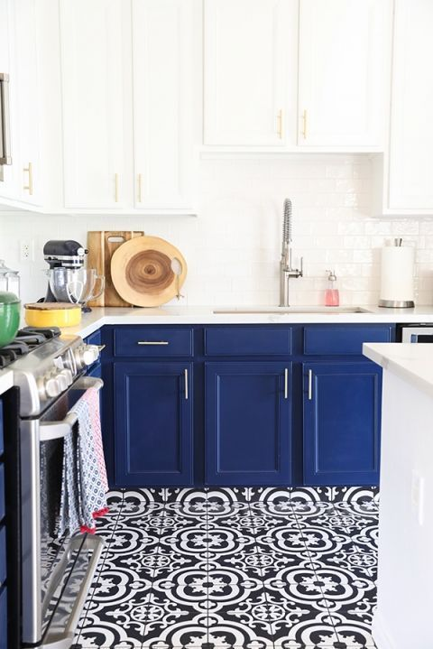 a chic and bold kitchen with navy cabinets and white countertops and mosaic navy and white tiles on the floor