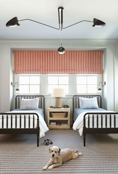 a chic shared guest bedroom with a tirple window covered with a coral shade and a printed rug