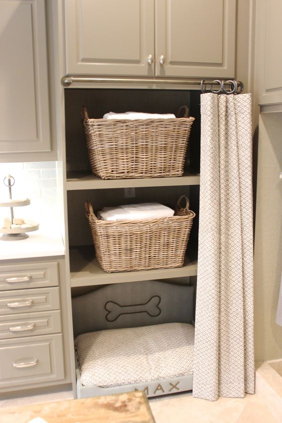 a laundry room with storage cabinets and an incorporated dog bed for your pet to relax while you are doing things