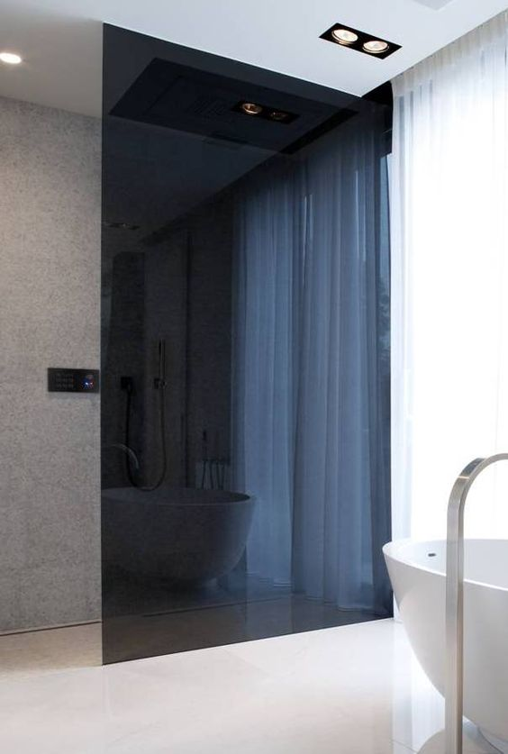 a minimalist bathroom with a smoked glass shower to separate the space gently and with an edgy feel