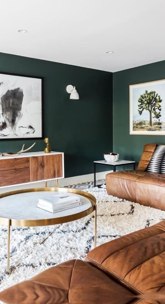 dark green walls contrast warm brown leather furniture and make the living room very relaxing