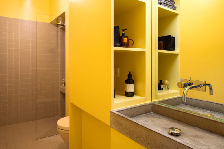 The bathroom combines yellow and greys - grey tiles and a concrete sink