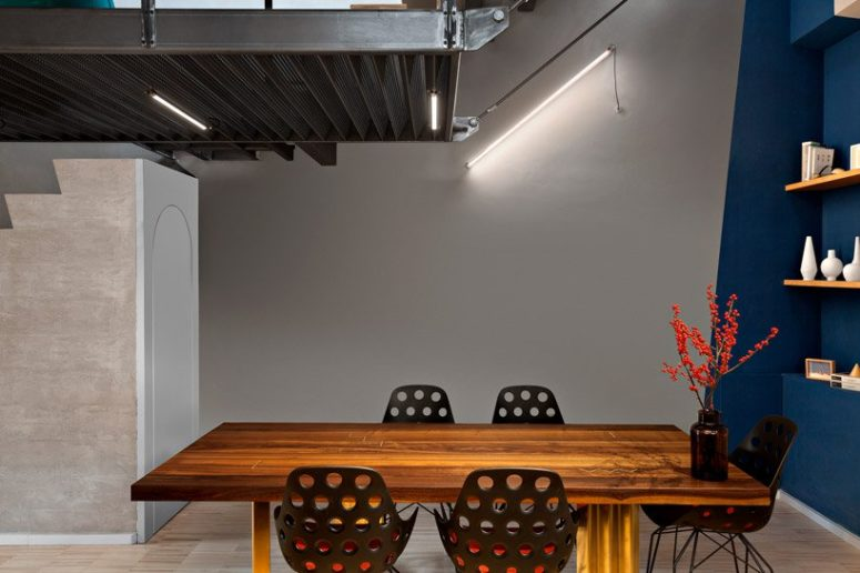 The dining space features geometric decor, industrial lighting, a bold dining table and metal perforated chairs