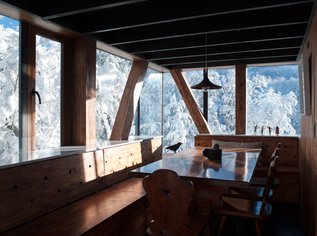 The dining space is fully of wood and there are non framed windows to catch the views while eating here