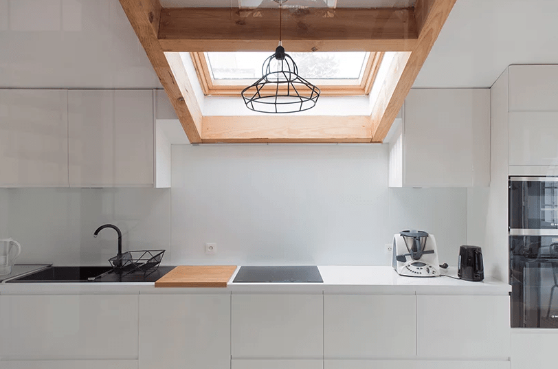 The kitchen is done with sleek white cabinets, wooden touches, black items for a contrast and a skylight