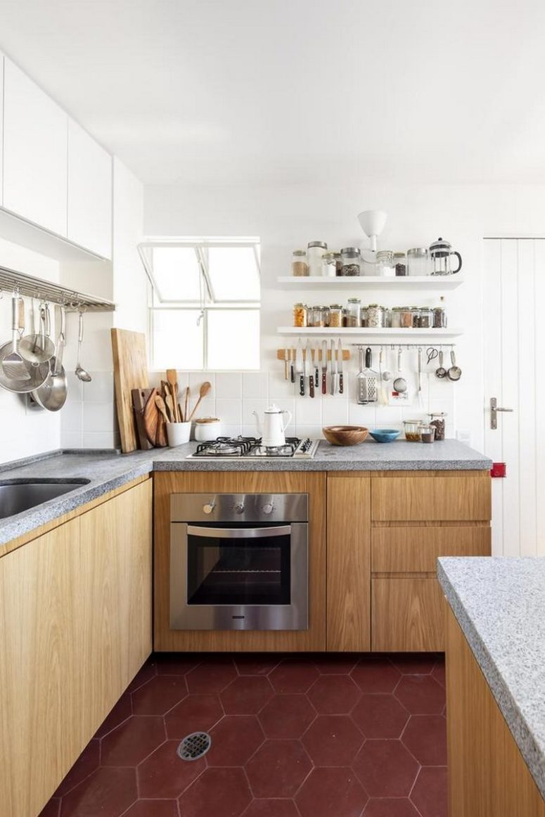 The kitchen is done with white and wooden cabinets, with concrete countertops and a white tile backsplash