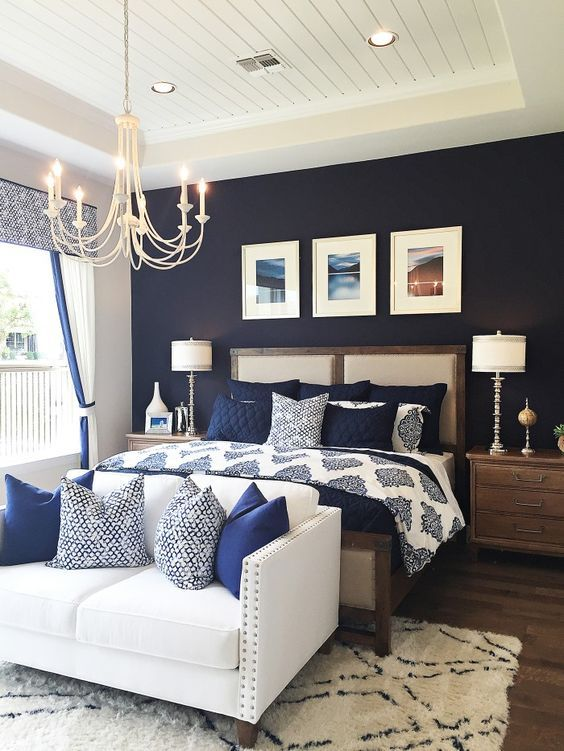 a bedroom with a navy statement wall, navy and white bedding and a creamy couch with navy pillows