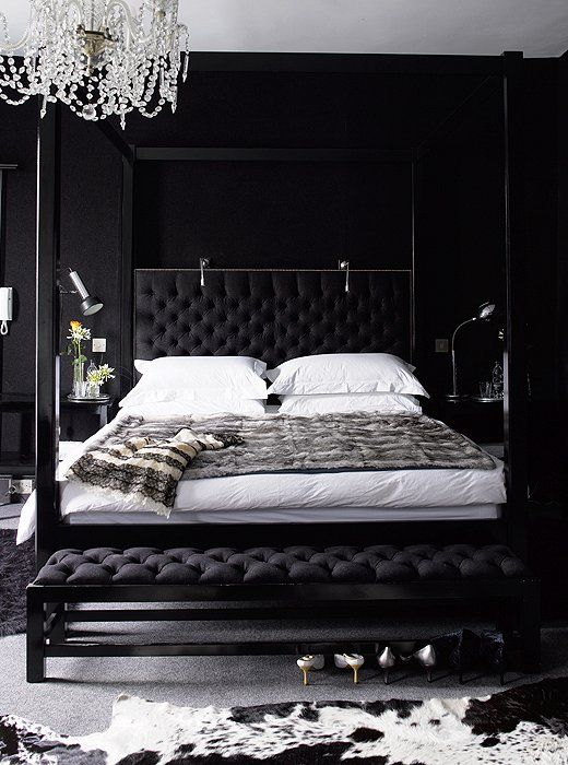 a dark glam bedroom done in black, with white bedding and touches of grey is a chic idea