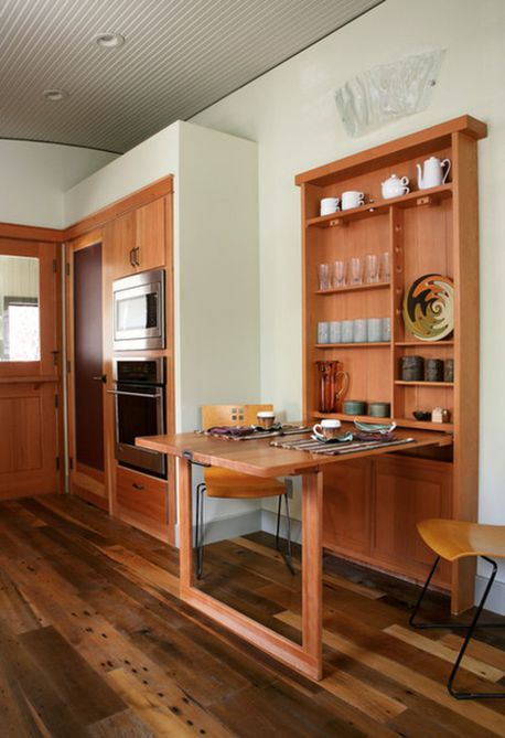 a dining space with storage and a wall-monted table desk that cna be hidden any time