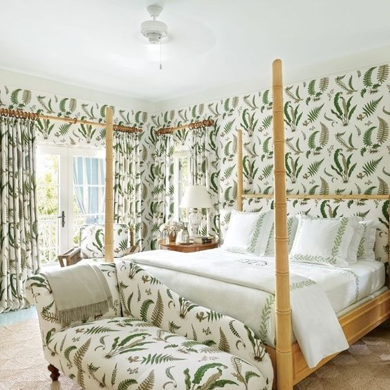 a stylish daybed at the foot of the bed features the same print as the walls and curtains in this cool feminine bedroom
