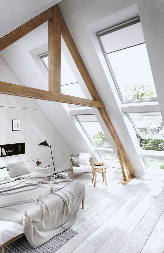 an off-white attic bedroom with stained wooden beams and all-neutral textiles and furniture
