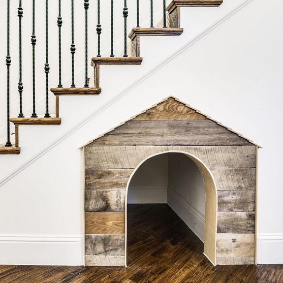 build in a dog house under the staircase to give him or her a personal space while being around you at the same time