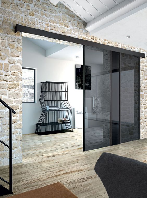 smoked glass sliding doors stand out in stone clad giving it a fresh and more modern look