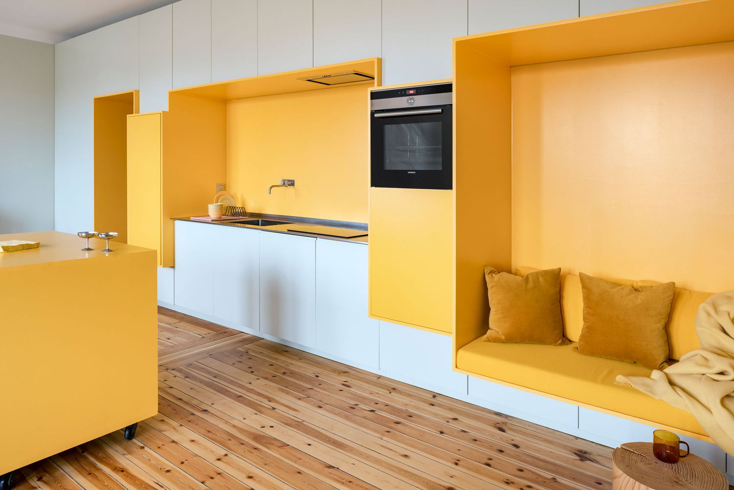 A yellow seat features an integrated kitchen unit and a comfy seat with pillows