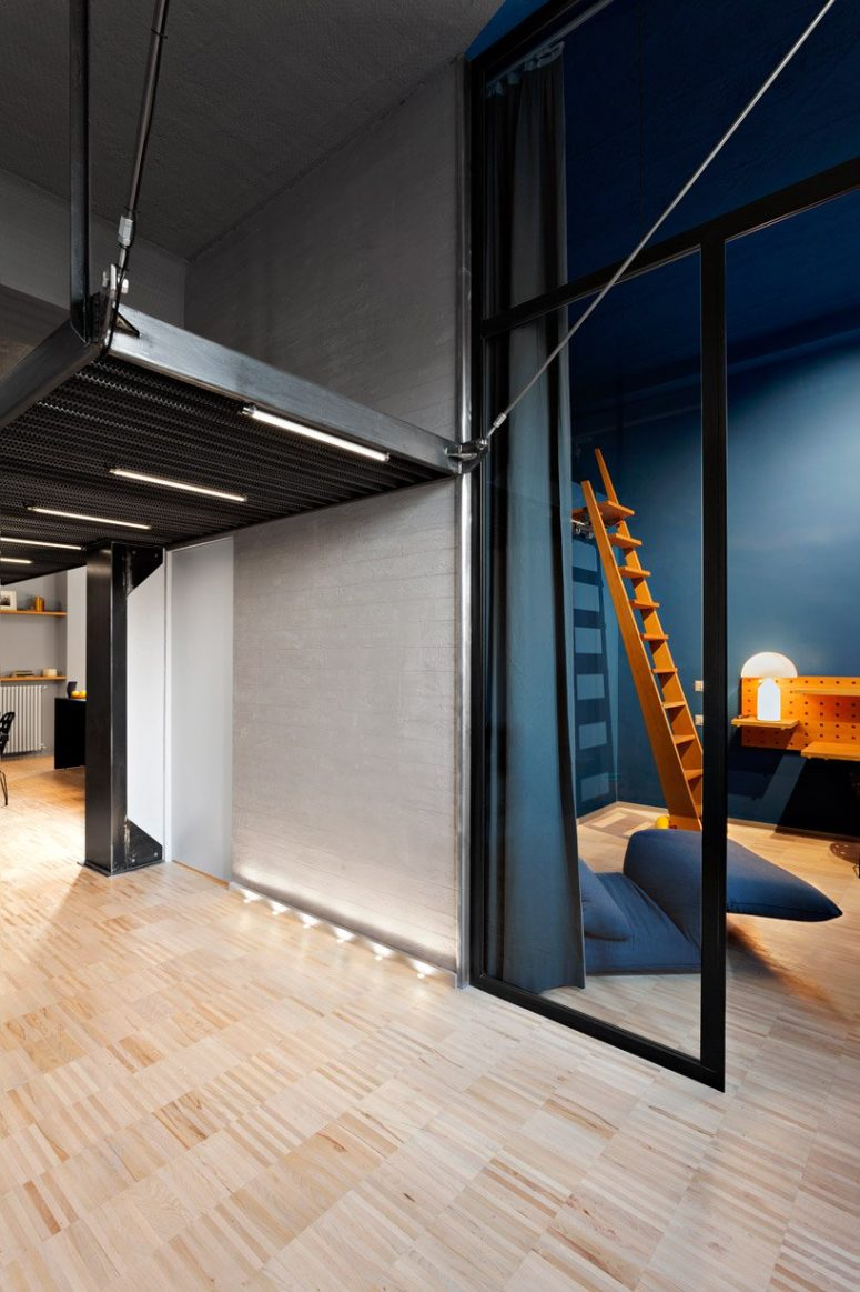 Much light, lots of blues and navy details, industrial touches make the space modern and refined