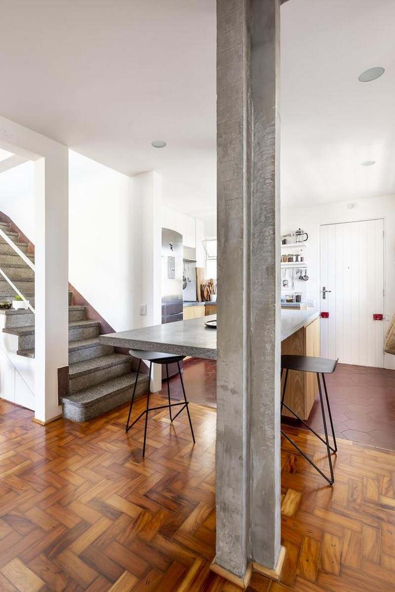 The dining space doubles as a kitchen island made of wooden cabinets and a concrete countertop