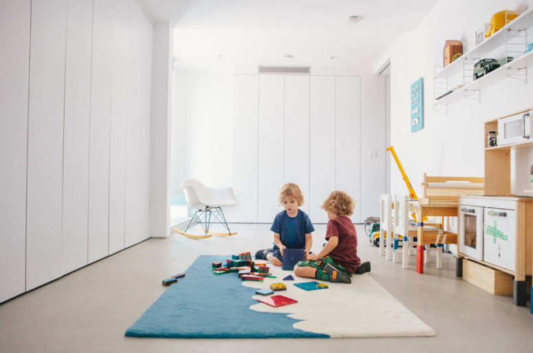 The kids' room is done with hidden storage inside white cabients and there's some comfy kids' furniture and bright touches